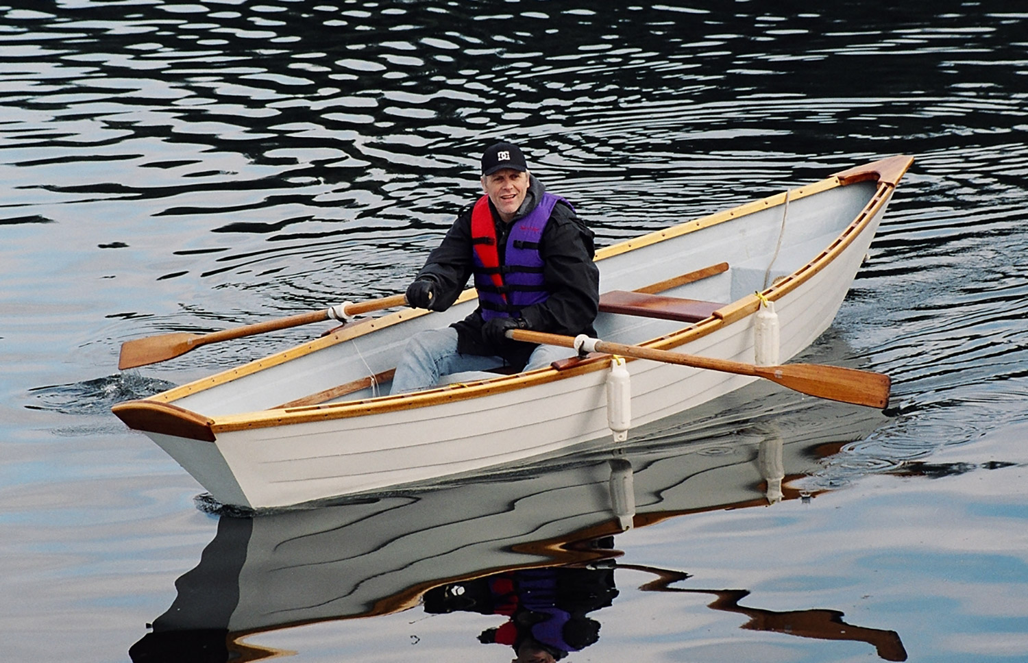 Man with cap and lifevest in a rowboat